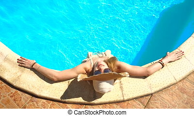 a young girl with a hat stands in the pool looking up put your hands on the sides and adjusts her glasses