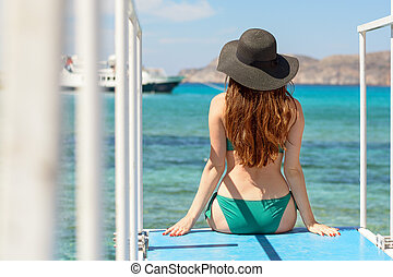 A young girl with a hourglass figure sits on a pier and looks into the sea. wearing a green swimsuit and a black hat. rear view.