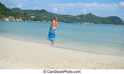 a young girl with a pareo is along the shore of the beach....