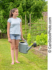 young girl with a watering can in the garden