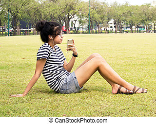 A young girl with headphones outdoors. Listening music