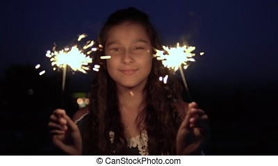 A young girl with long dark hair stands with fireworks in her hands against the backdrop of the night city. slow motion.