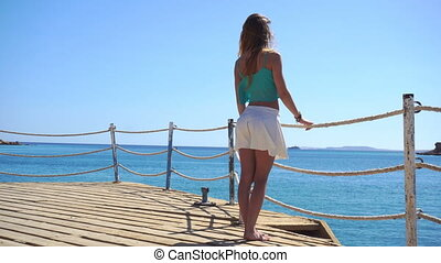 girl with long hair and a white skirt stands on the pier and looking at the sea