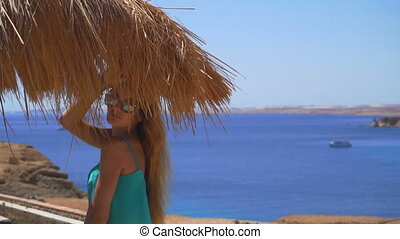 a young girl with long hair and glasses stands in the summer under the bungalows near the sea in slow motion