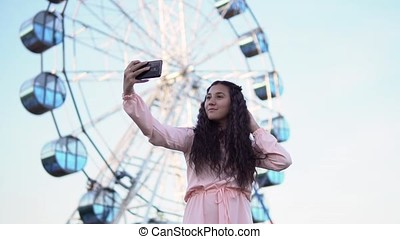 A young girl with long hair in a dress makes selfie using a smartphone standing near the Ferris wheel. slow motion.