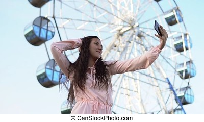 A young girl with long hair in a long dress makes selfie using a smartphone standing near the Ferris wheel. slow motion.