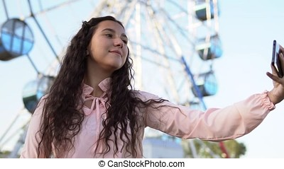 A young girl with long hair in a pink dress makes selfie using a phone while standing near the Ferris wheel. slow motion.