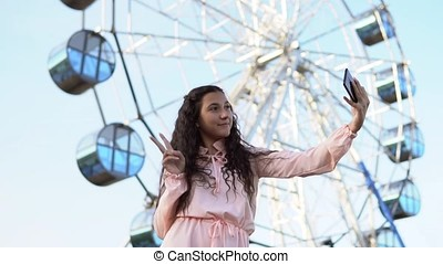 A young girl with long hair in a pink long dress makes selfie using a phone while standing near the Ferris wheel. slow motion.