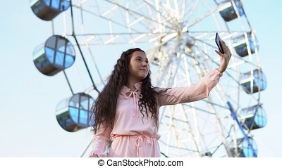 A young girl with long hair in a pink long dress makes selfie using a smartphone standing near the Ferris wheel. slow motion.
