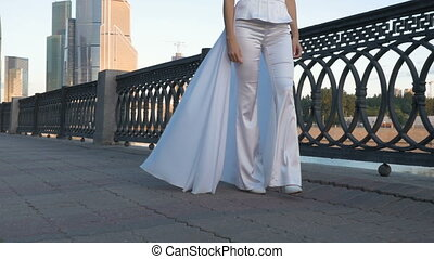 A young girl with long hair, in a white suit, walks along the city embankment.