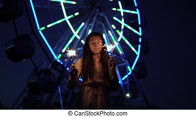 A young girl with long hair stands against the background of a city at night and holds fireworks in her hands. slow motion. HD