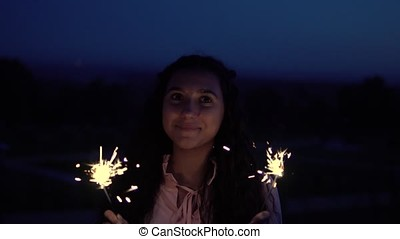 A young girl with long hair stands with fireworks in her hands against the background of a night city. slow motion.