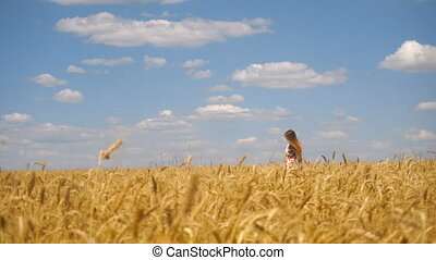 a young girl with long hair walks on wheat field