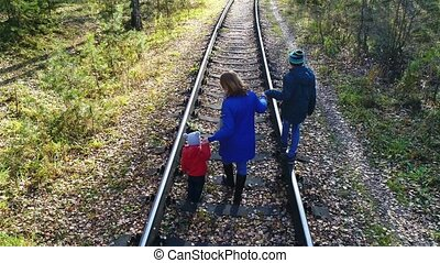 A young girl with two children walking on the railroad. A walk outdoors in the fall.