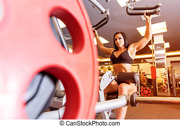A young girl working out at a weight lifting machine in the Gym