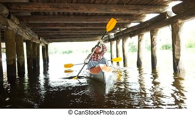 A young girl works hard with a paddle in a kayak on the...