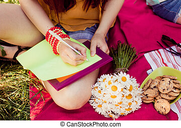 a young girl writes a pen in notebook outdoors