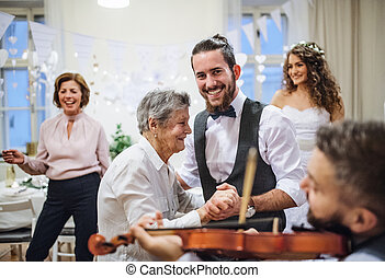 A young groom dancing with grandmother on a wedding reception.