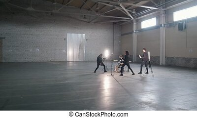 A young group playing rock music in a hangar. Mid shot