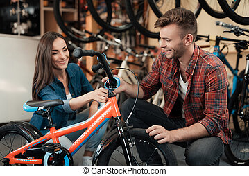 A young guy and a girl are choosing a children's bicycle.