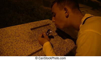 a young guy drinks water from a fountain in the evening.