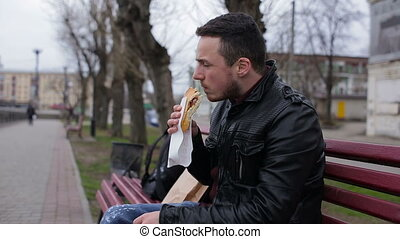 A young guy eat hotdog in the city on a bench