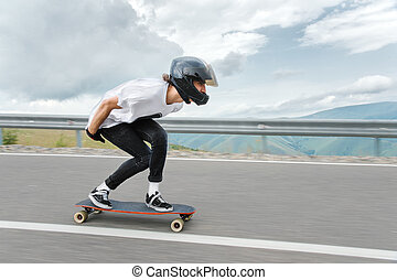 A young guy in a full-face helmet is riding on a country road at high speed in the rain