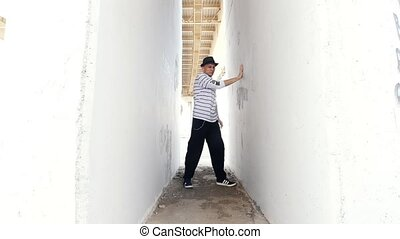 A young guy in a hat dancing popping between two white walls...