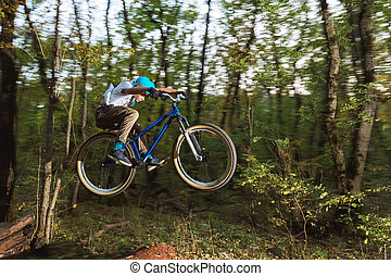 a young guy in a helmet flies on a bicycle after jumping from a kicker