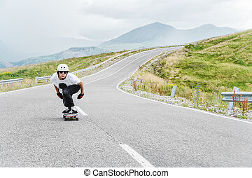 A young guy in helmet is riding on a country road at high speed in the rain