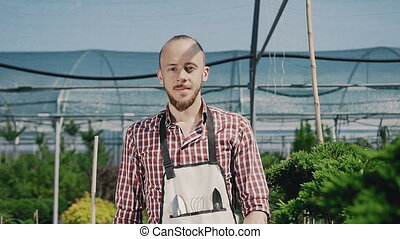 A young guy is a gardener in mittens and a garden apron, smiling and posing on the camera. Large greenhouse of ornamental plants and flowers. Slow camera.
