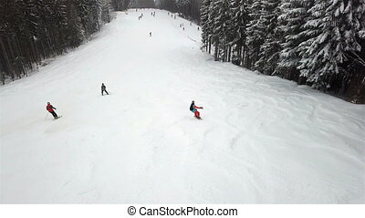 A young guy is riding a snowboard down the alpine slope