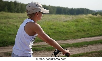 A young guy is sitting on a bicycle.