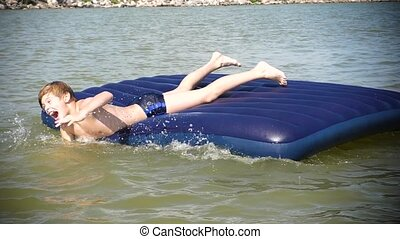 A young guy is swimming in the sea on an inflatable mattress. Positive emotions. Hot summer day
