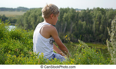 a young guy sits on the banks of the river. Beautiful summer landscape