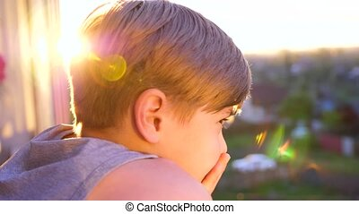 A young guy stands near the window and looks at the sunset. The sun's rays illuminate the room