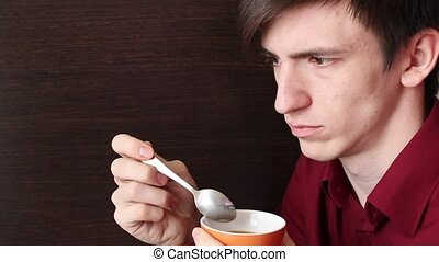 A young guy takes out a spoonful of tea on the edge of the mug and licks it with his mouth