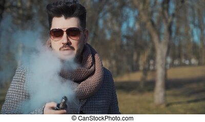 A young handsome bearded hipster man vaping an electronic cigarette in the park in the spring. Close up.