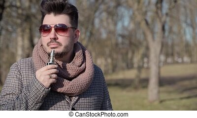 A young handsome bearded hipster man vaping an electronic ...