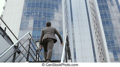 A young handsome Businessman climbing stairs to the business...