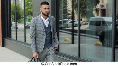 A young handsome businessman student in a suit, comes with a...