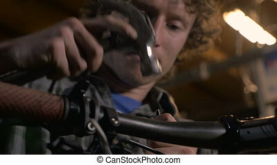 A young handsome man carefully uses a hammer to repair...