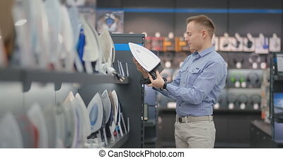 A young handsome man examines the iron in the store to buy a...