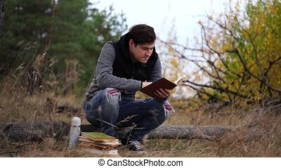 A young handsome man in casual clothes is sitting on a log ...