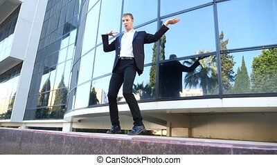 A young happy businessman in a business suit dancing modern ballet and wacking against the backdrop of a business center building. Slow-mo