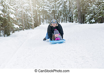 Young happy father and her daughter enjoying a sledge ride