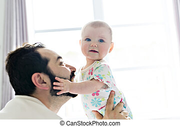 Young happy father playing with babyon bed