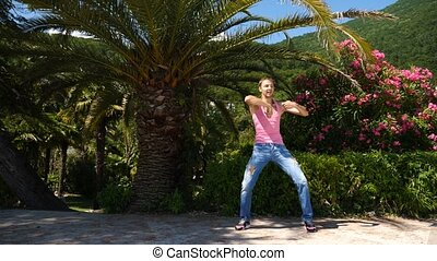 A young happy guy dancing modern ballet and wacking in a summer park. slow-mo