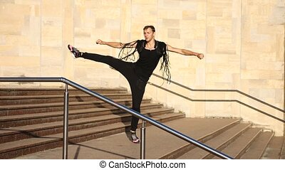 A young happy guy dancing modern ballet and wacking on the stairs in the street. slow-mo