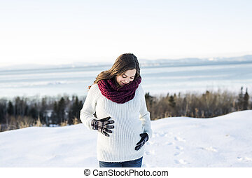 Young happy pregnant woman in snowy forest